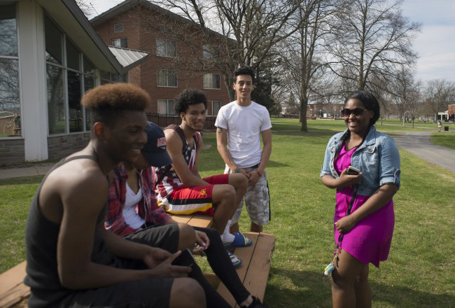 Students laughing at campus picnic tables in Spring 068
